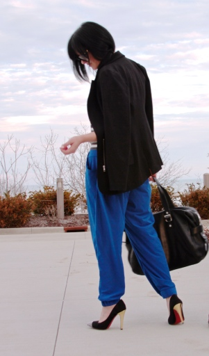 Sporty blue trousers paired with conservative blazer, high heels and duffel bag.